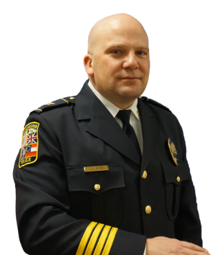 Chief Kelly posing with his right arm bent across his stomach as if leaning on a bar and a smile