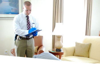 A detective in a white shirt and tie investigating a crime scene in a hotel room type scene holding a clipboard wearing blue latex gloves
