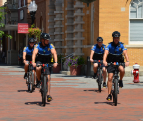 Four officers patroling on a sunny day riding their special issued bicycles on a brick paved street.