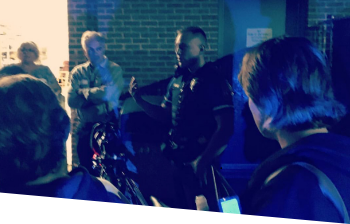 An officer giving a lecture at night outside with his motorcycle beside him