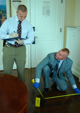 A couple of detectives investigating a crime scene, one standing writing on a clipboard and the other knealt down with measuring tape to the floor
