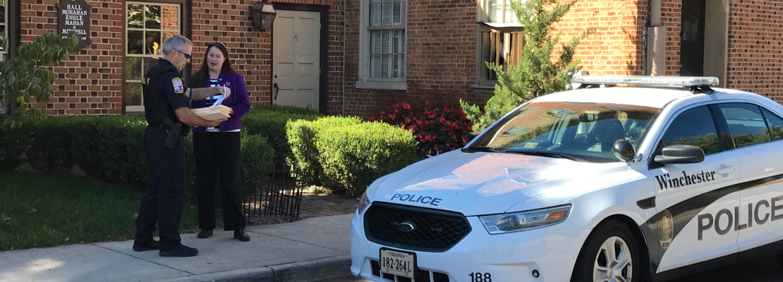 An officer speaking with a potential witness out front of a residential style office building with his cruiser parked close by.
