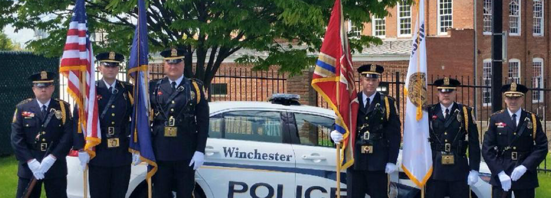 Six officers in full uniform with four of them holding flags, all standing in front of a police cruiser parked in front of the Winchester Police Department