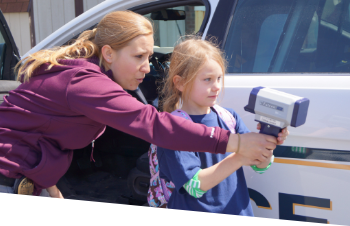 A female officer shows a young girl how to use a radar gun