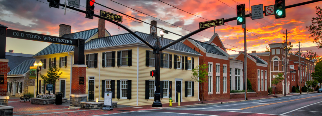 A photo of Old Town Winchester at the corner of Cork street and Loudoun street with a large yellow house as the focus during an orange sunset