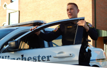 An officer standing and looking forward diligently with his hands on top of the open driver side door of his patrol car as if he just opened it.