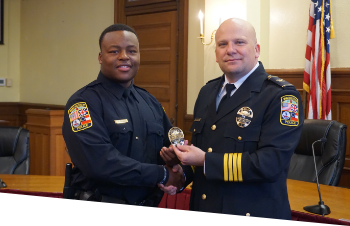 The Chief of Police giving a new officer his badge at initiation