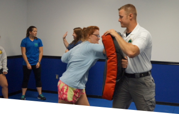 A teen girl practicing self defense with as an instructor holds a boxing/kick pad